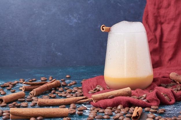 Grains de café avec une tasse de boisson sur bleu.