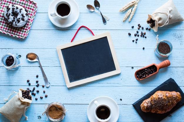 Grains de café et tasse de café avec d'autres composants sur différents fond en bois.