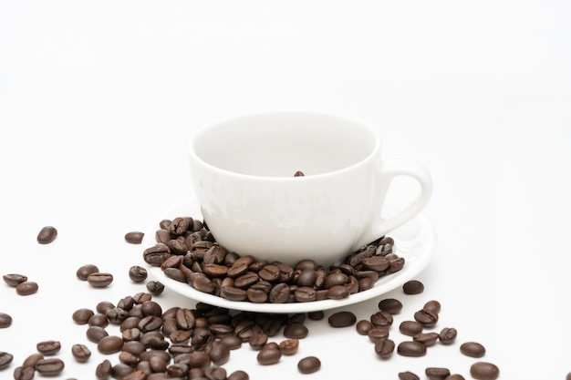 Grains de café et tasse à café blanc isolé sur fond blanc.