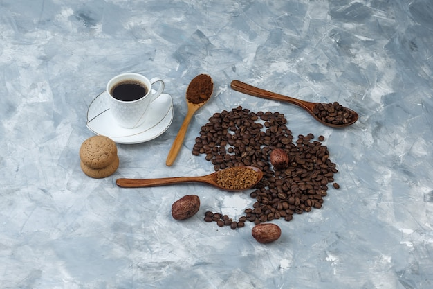 Grains de café, tasse de café avec café instantané, farine de café, grains de café dans des cuillères en bois, cookies high angle view sur un fond de marbre bleu clair