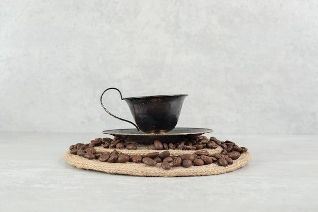 Grains de café et tasse de café sur morceau de bois