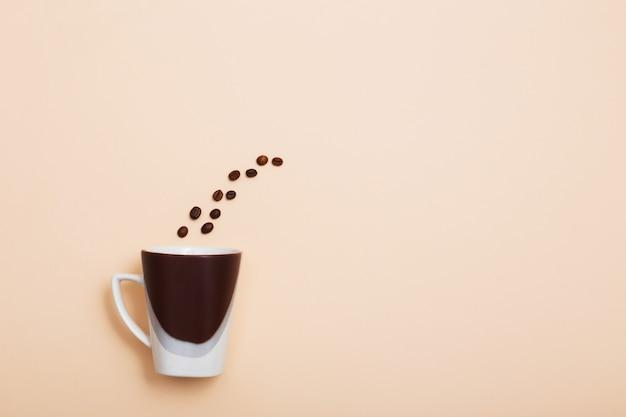 Grains de café et une tasse sur fond clair