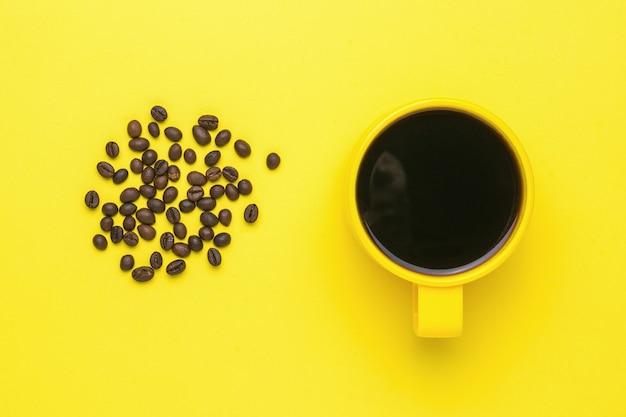 Grains de café et une tasse jaune avec un verre sur fond jaune. une boisson chaude populaire et un équipement pour la créativité.