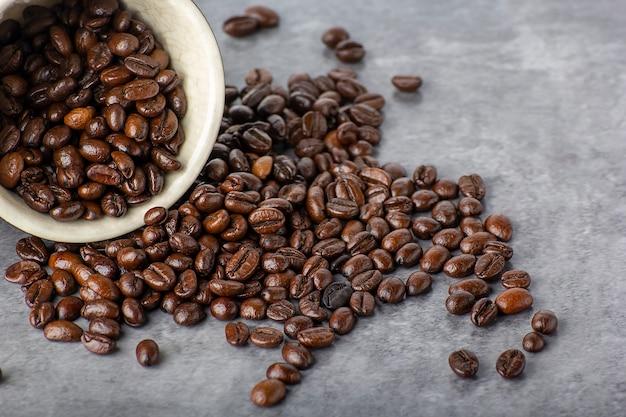 Grains de café et tasse noire blanche