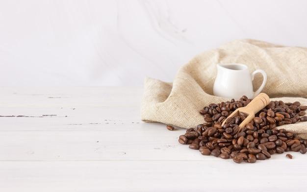 Grains de café, toile de jute et pot à lait avec crème