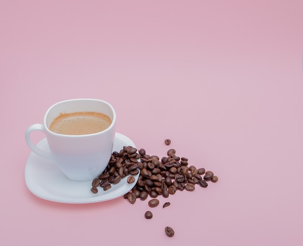 Grains de café torréfié dispersés dans une tasse sur fond rose, copiez l'espace.