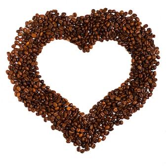 Grains de café torréfiés sur blanc. espace pour le texte en forme de coeur.