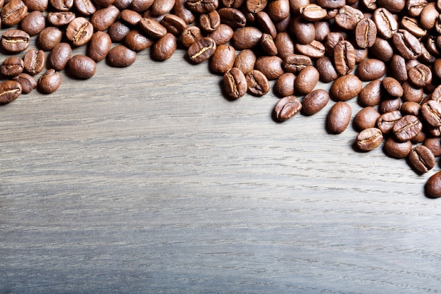Grains de café torréfiés sur bois. photo haute résolution.