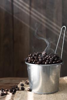 Grains de café torréfiés en boîte galvanisée sur table en bois grunge