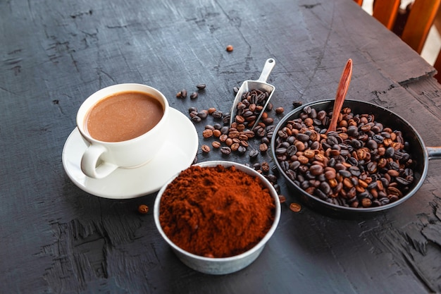 Grains de café torréfiés avec café en poudre et tasses à café.