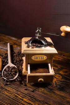 Grains de café torréfiés, cuillère en bois et moulin à main