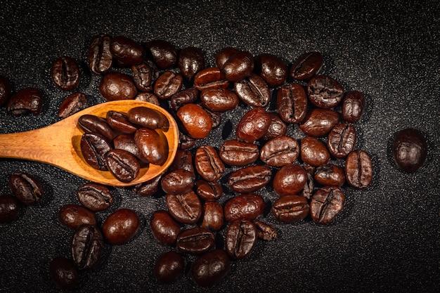 Grains de café torréfiés avec une cuillère en bois