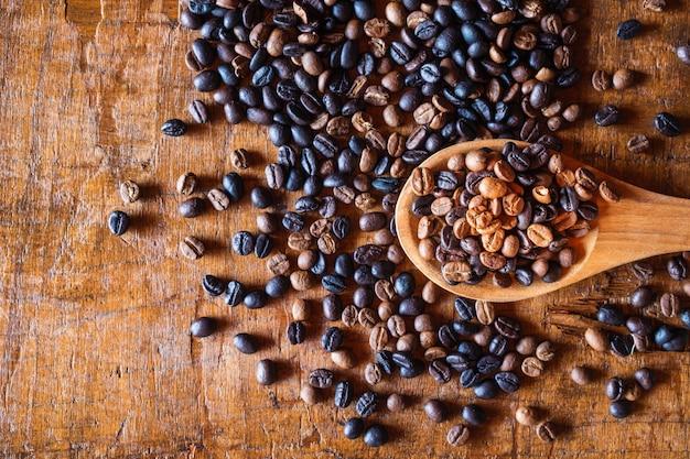 Grains de café torréfiés sur une cuillère en bois