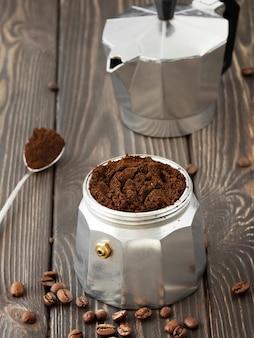 Grains de café torréfiés dans un bocal en verre, éparpillés sur une table en bois brun