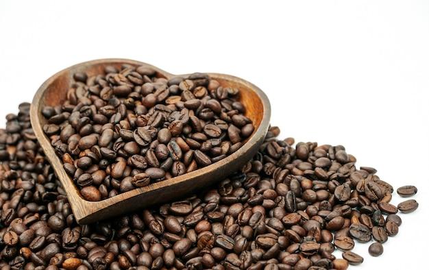 Grains de café torréfiés dans un bol en bois en forme de coeur isolé sur fond blanc