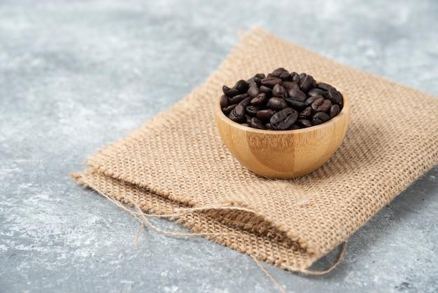 Grains de café torréfiés dans un bol en bois sur marbre.