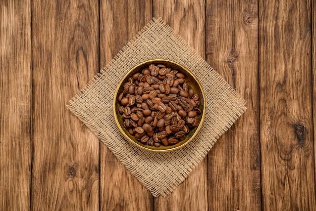 Grains de café torréfiés dans un bol sur une table en bois