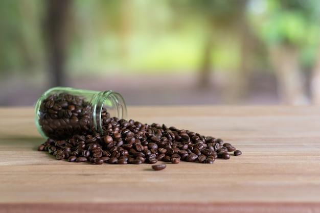 Grains de café torréfiés dans des bouteilles de verre placées sur la table avec le fond de la nature.