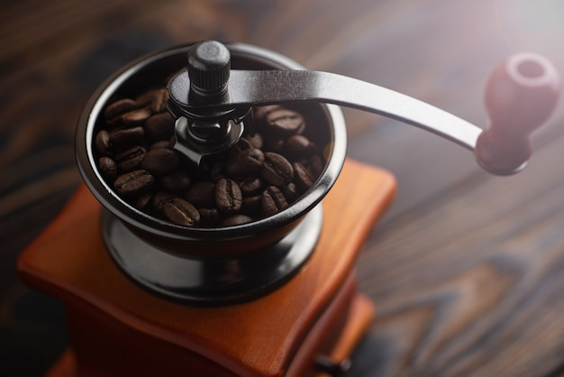 Grains de café torréfiés dans un moulin à café. préparation du café pour l'infusion.