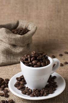 Grains de café torréfiés dans une tasse blanche