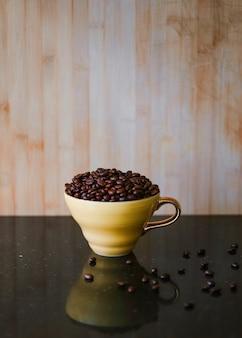 Grains de café torréfiés dans une tasse en céramique brune sur un bureau réfléchissant