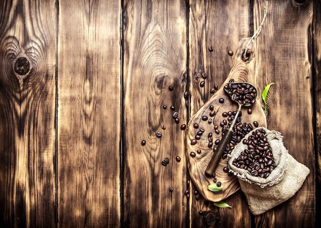 Grains de café torréfiés dans un vieux sac. sur fond en bois.