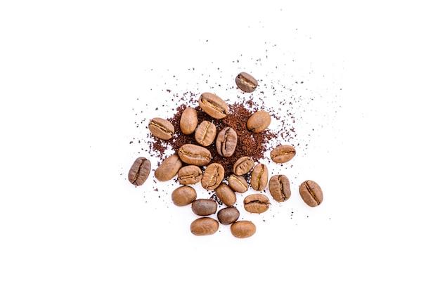 Grains de café torréfiés avec du café moulu sur blanc