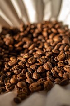 Grains de café torréfiés sur filtre à café en papier.