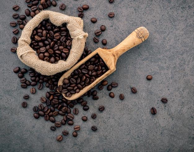 Grains de café torréfiés foncés sur pierre.