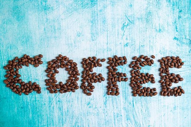 Grains de café torréfiés sur fond aigue-marine