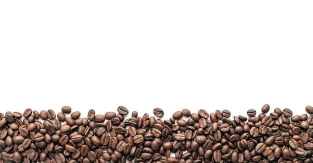 Grains de café torréfiés sur fond blanc. fermer.
