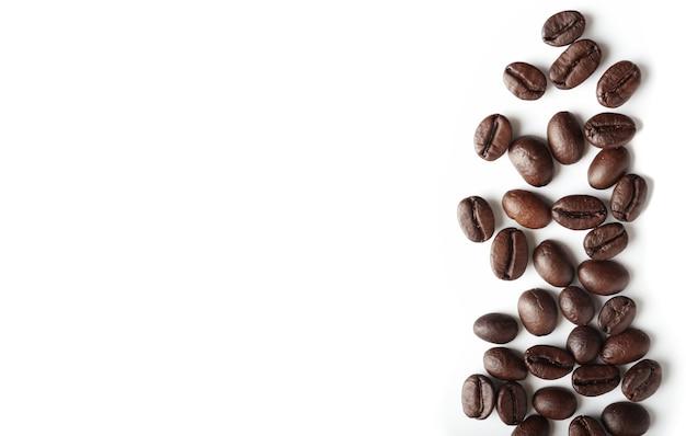 Grains de café torréfiés sur fond blanc