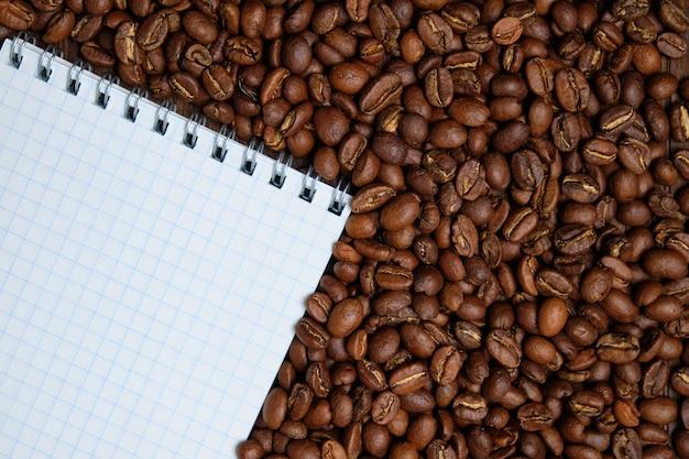 Grains de café torréfiés avec fond de bloc-notes papier