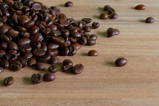 Grains de café torréfiés sur fond de bois.