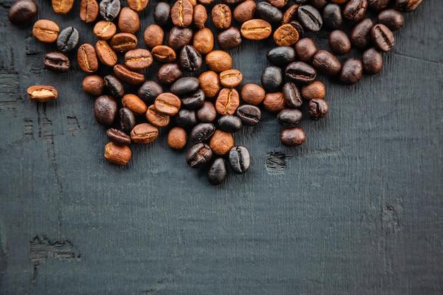 Grains de café torréfiés sur fond noir, vue du dessus