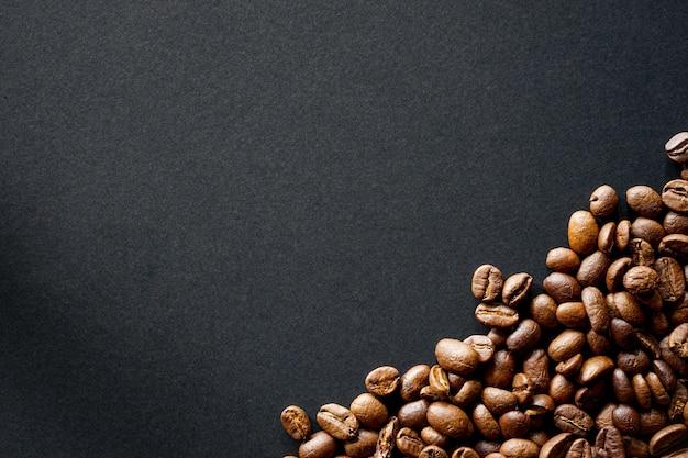 Grains de café torréfiés sur fond noir