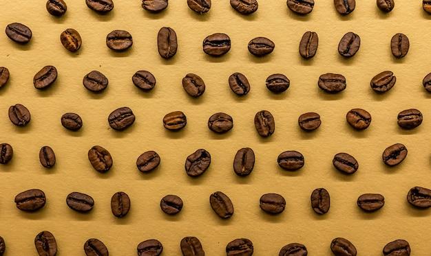 Grains de café torréfiés sur fond d'or brillant, peuvent être utilisés comme papier peint