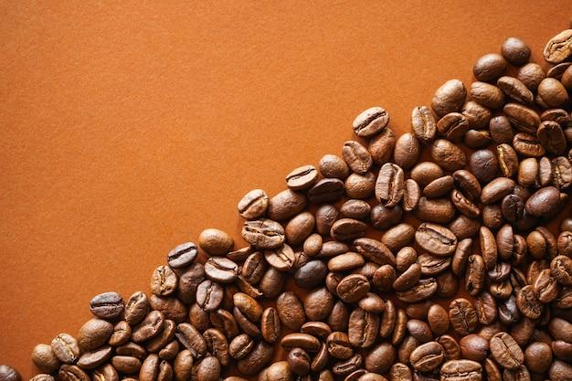 Grains de café torréfiés sur fond de papier brun