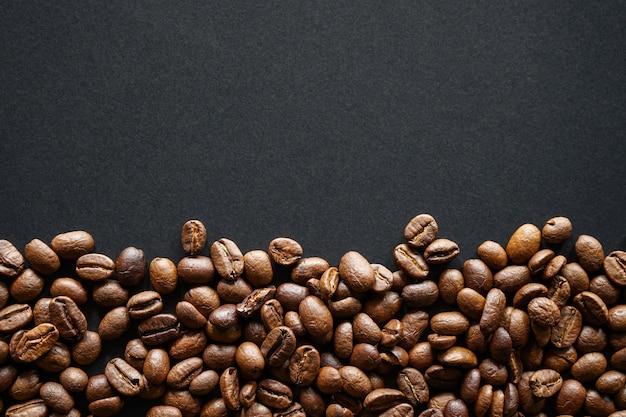 Grains de café torréfiés sur fond de papier noir