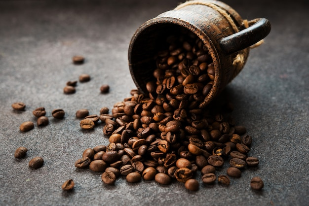 Grains de café torréfiés sur fond sombre, gros plan, mise au point sélective