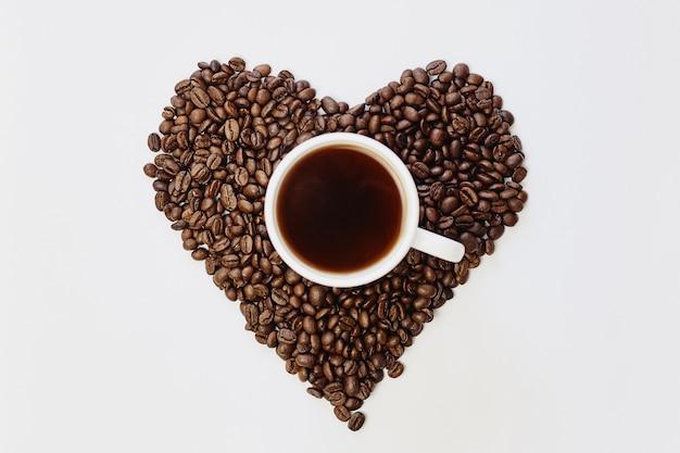 Grains de café torréfiés en forme de coeur et tasse de café blanc