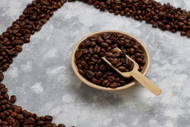 Grains de café torréfiés frais sur béton, vue de dessus, plat poser