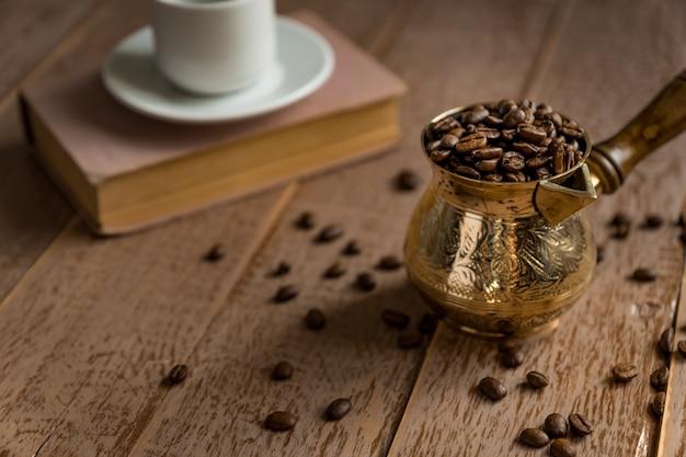 Grains de café torréfiés frais en cezve (pot de café turc traditionnel) livre fermé et tasse sur table en bois.