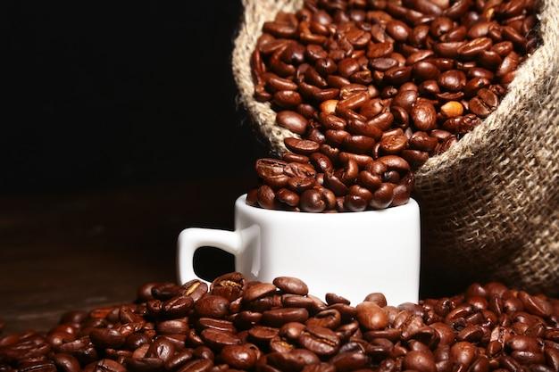 Grains de café torréfiés frais dans un sac en jute, une tasse à café et un moulin sur fond sombre.