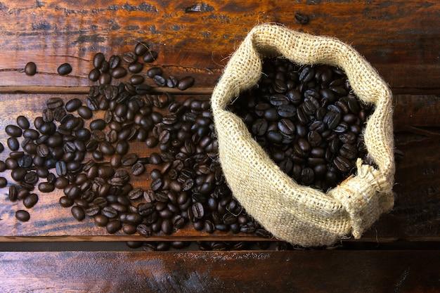 Grains de café torréfiés et frais dans un sac en tissu rustique et versés sur une table en bois rustique. vue de dessus