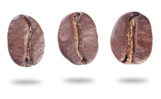 Grains de café torréfiés frais isolés sur fond blanc.