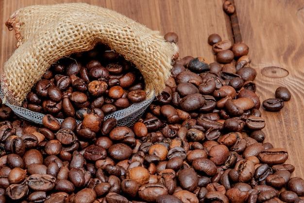 Grains de café torréfiés frais tombant du sac sur la surface en bois. grains de café brun éparpillés du sac sur la table