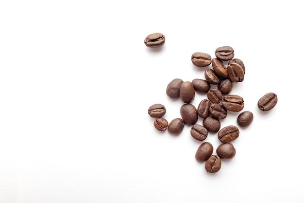 Grains de café torréfiés isolés sur fond blanc. fermer.