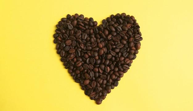 Grains de café torréfiés isolés en forme de coeur sur le mur jaune vue de dessus