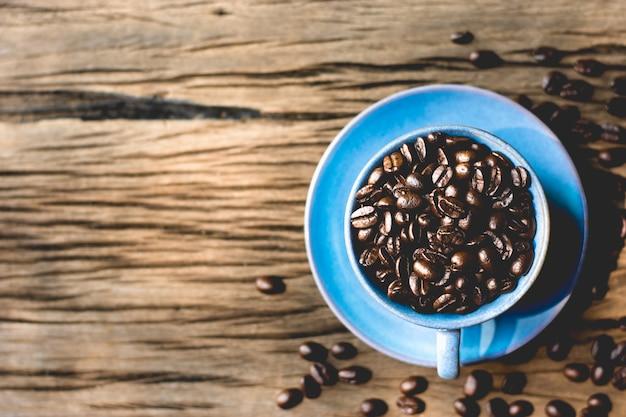 Grains de café torréfiés mis dans une tasse à café bleue.